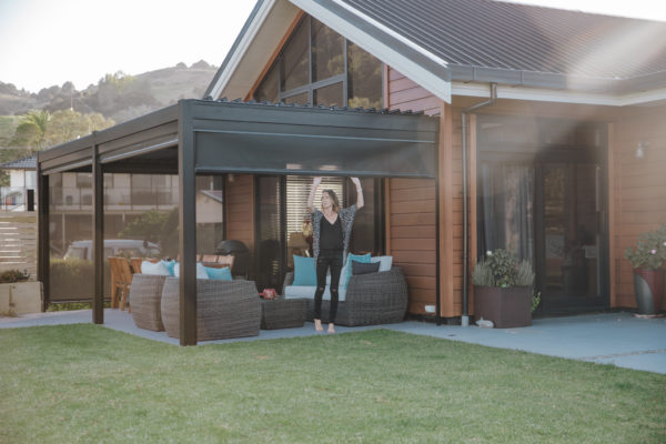Woman pulling down side screening of louvered roof